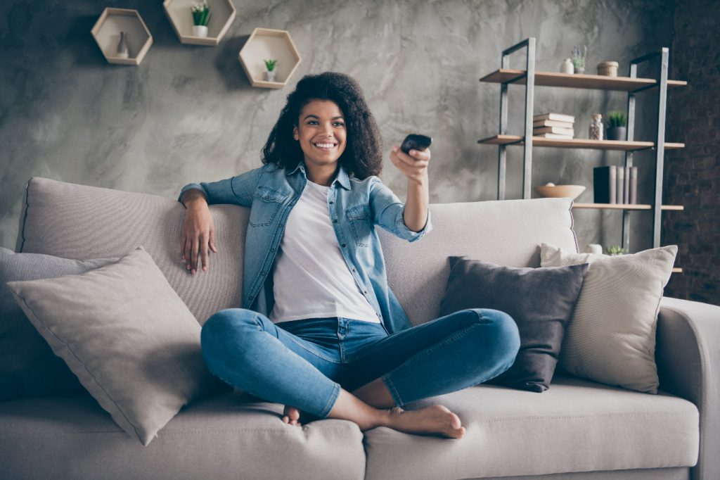 pretty lady holding tv remote control changing channel