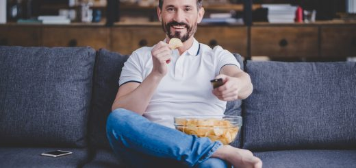 smiling man watching tv and eating chips at home