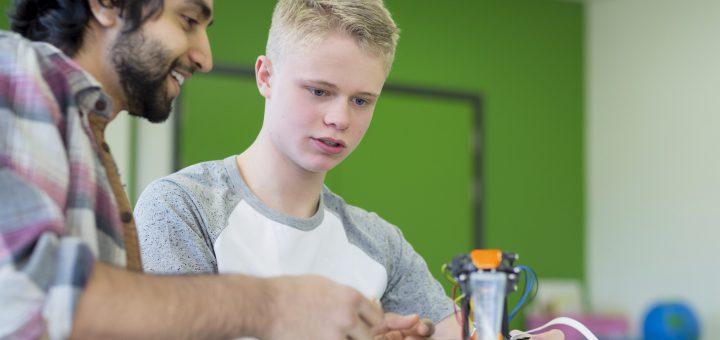 Teacher and student building a robotic arm