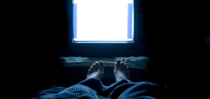 person watches TV at night in his bed