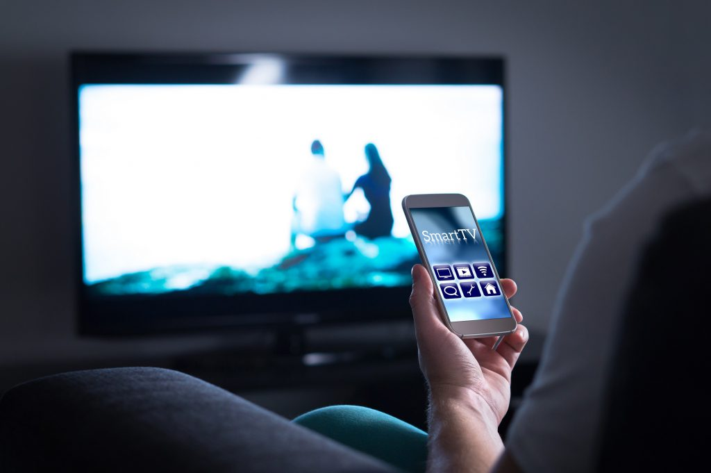 man watching television and using tv remote application on mobile
