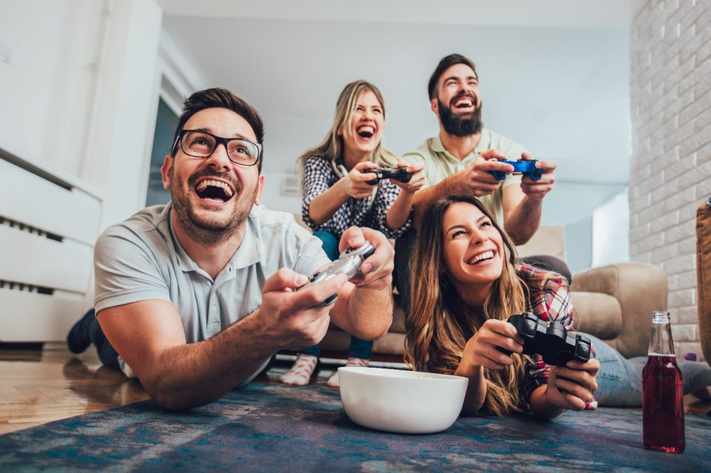 group of friends play video games together at home