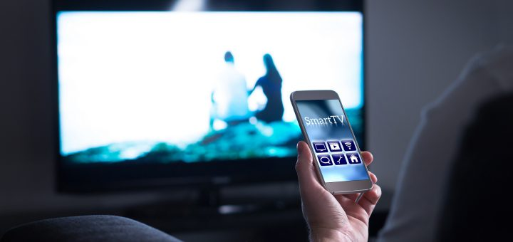 Man watching television and using smart tv remote control app on mobile
