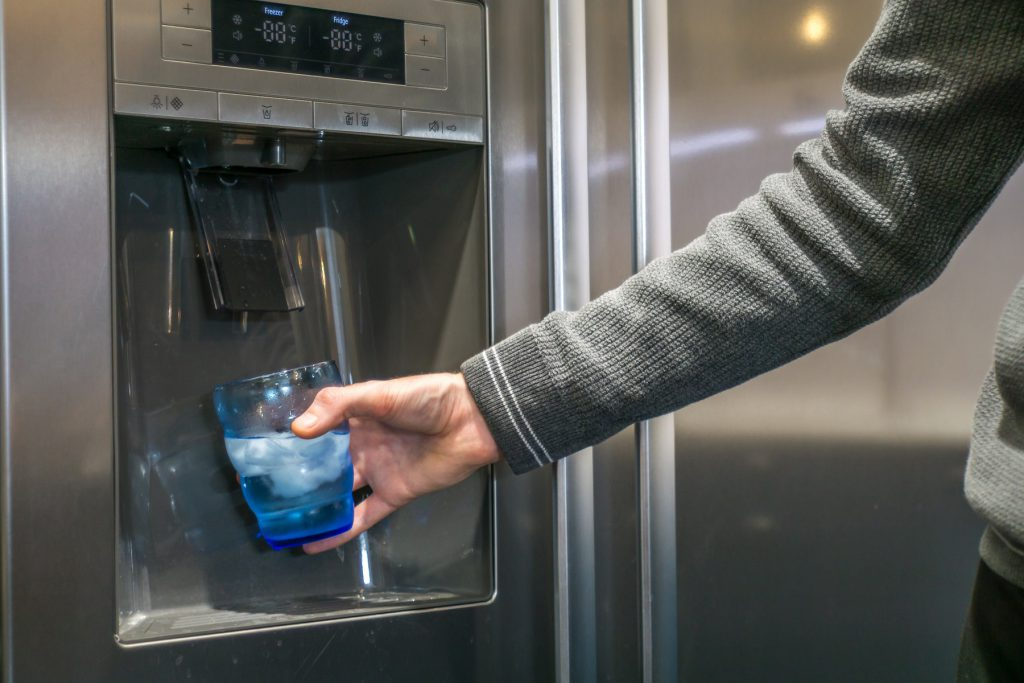 Male hand is pouring water and ice cubes from dispenser of fridge