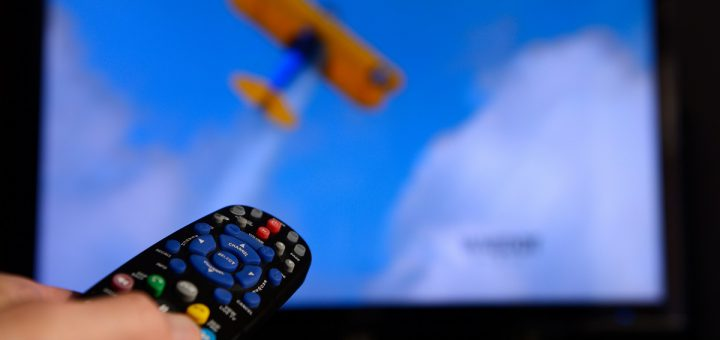 Man pointing a universal remote control towards a television screen