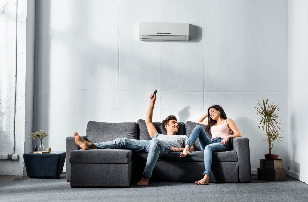 handsome boyfriend switching on air conditioner and looking at smiling girlfriend