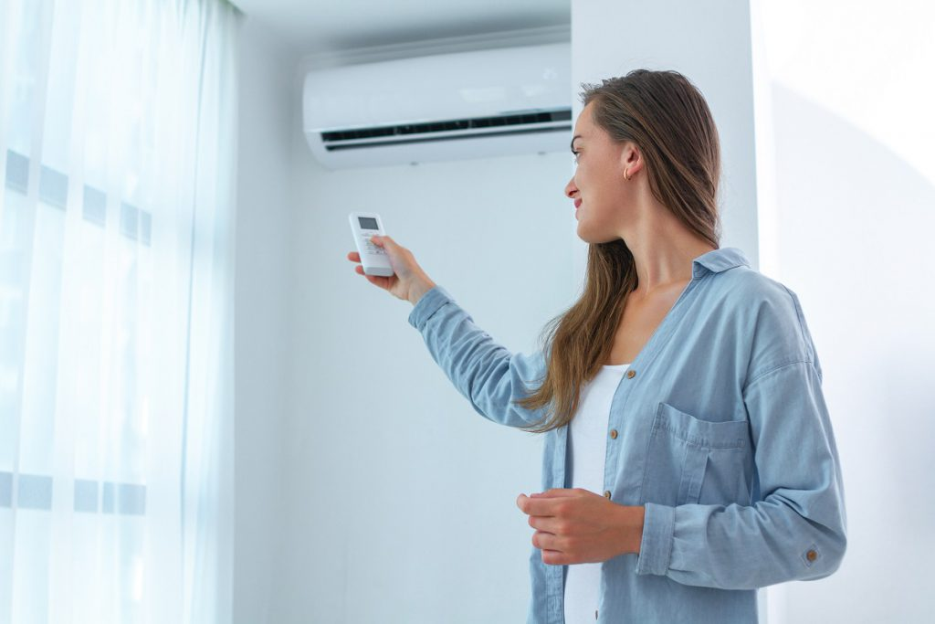 Young woman adjusts the temperature of the air conditioner using the remote control