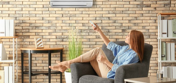 Young woman switching on air conditioner while sitting in armchair