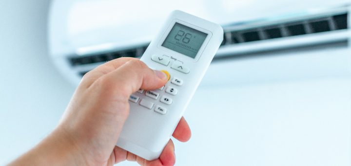 Air conditioner temperature adjustment with remote controller in room at home