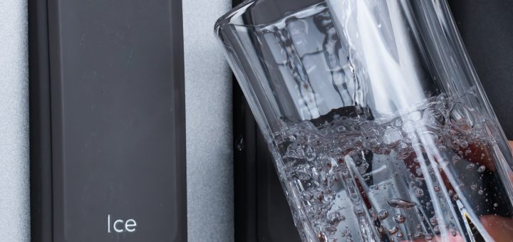 hand with a glass of water against a water dispenser in the fridge